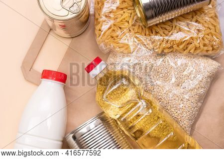 Paper Bag With Food Supplies Crisis Food Supply On A Light Yellow Background. Pearl Barley, Pasta, M