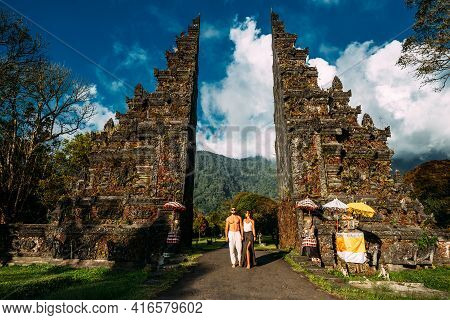 Beautiful Couple At The Bali Temple. Man And Woman Traveling In Indonesia. Couple At The Bali Gate.