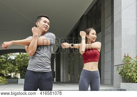 Positive Young Asian Couple Stretching Arms After Jogging Outdoors