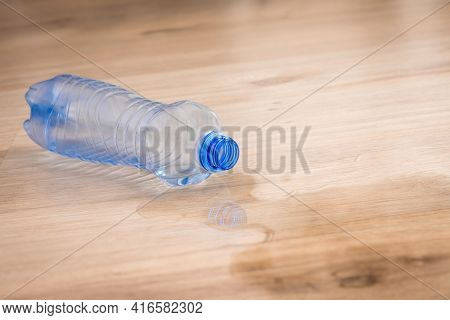 Spilled Water And Fallen Plastic Bottle On Wooden Laminate Floor