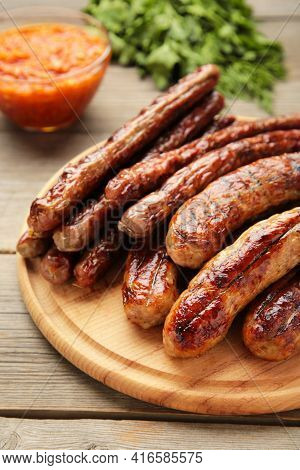 Grilled Sausages On Wooden Board On Grey Background. Top View. Vertical Foto