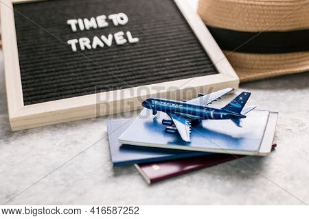 Top View Of Traveler Accessories With A Hat, Passport , Plane. Preparation For Travel. Traveling Jou