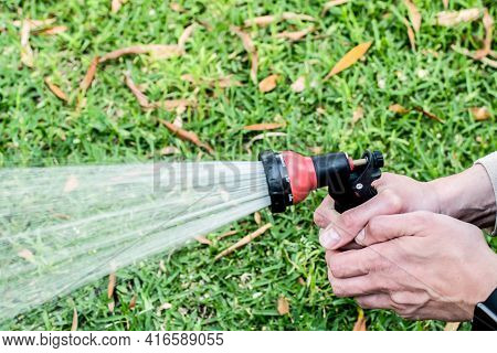 Watering The Lawn With The Garden Hose. Hands Holding Water Hose