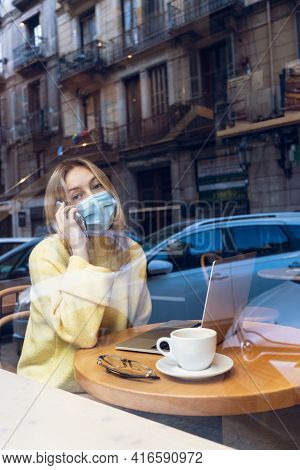Young Blond Woman With A Face Medical Mask Talking Mobile Phone And Working In Cafe. Freelance And O