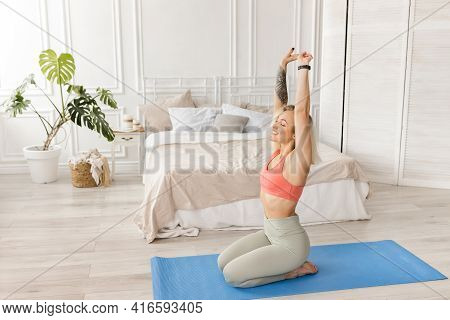 Happy Sportive Girl Doing Morning Exercises On Blue Mat At Home. Attractive Blonde-hair Woman Is Str