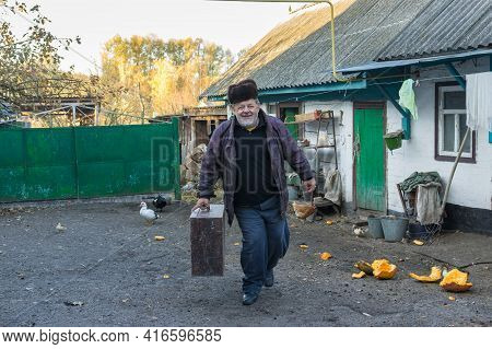 Positive Ukrainian Senior Peasant Carrying Huge Ancient Trunk While Walking On  The Homestead