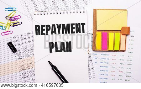 A Notebook With The Words Repayment Plan, A Marker, Colored Paper Clips And Bright Note Paper Lie On