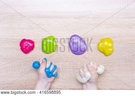 Multi-colored Slimes On The Table. The Child Plays With Slimes. Play Toy - Slime