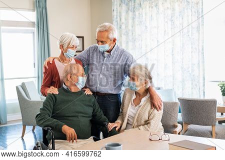 Group of senior men and old women wearing protective face mask and talking to each other at nursing home during quarantine. Disabled man and his friends wearing surgical mask at care facility centre.