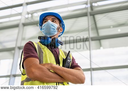 Mixed race young architect wearing covid-19 face mask while standing and looking around construction site. Proud indian architect inspecting construction site and working while wearing face mask.