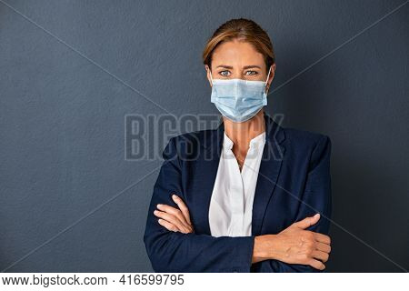 Portrait of happy businesswoman in formal clothing wearing face mask isolated against grey wall. Portrait of mature successful business woman with surgical face mask isolated on gray background.