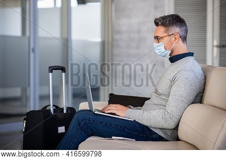 Mature businessman wearing protective face mask in airport during covid-19 pandemic while using laptop in waiting lounge. Entrepreneur working on laptop wearing covid-19 face mask at terminal airport.
