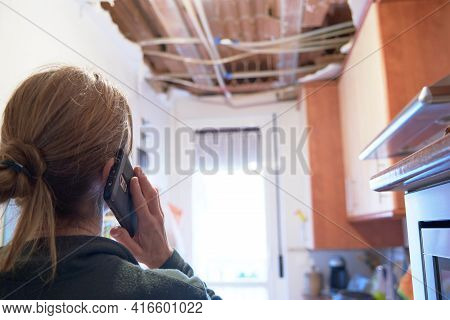Woman Explaining A Kitchen Ceiling Incident To Her Homeowner's Insurance Company.. Concept Of Accide