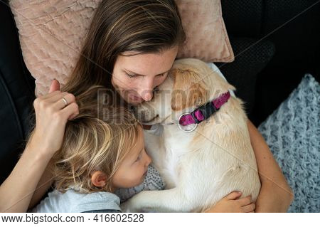 Top View Of Young Mother Cuddling With Her Toddler Daughter And Their Cute Dog On A Family Sofa.