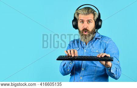 Play Computer Games. Man Bearded Hipster Gamer Headphones And Keyboard. Online Gaming Platform. Gami