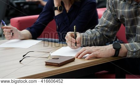 Adult Man And Woman Fill Out Paperwork Or Forms. The Concept Of Divorce Proceedings, Signing A Marri