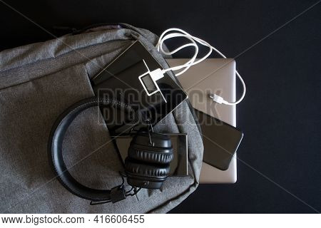 Lot Of Modern Gadgets: Smartphones, Laptop And Tablet Are In A Trendy Gray Textile Backpack Along Wi