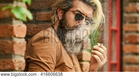 Day In Smoke. Go Out For Smoke Break. Handsome Stylish Man Smoking Outside In Urban Setting. Hipster