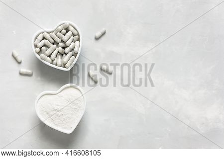 Collagen Powder And Tablets On A Gray Background With A Copy Space. Extra Protein Intake. Natural Be