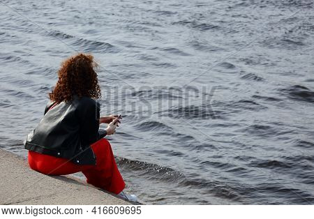 A Girl In Red Pants Sits On The Steps Of The River Embankment, Admiralteiskaya Embankment, St. Peter