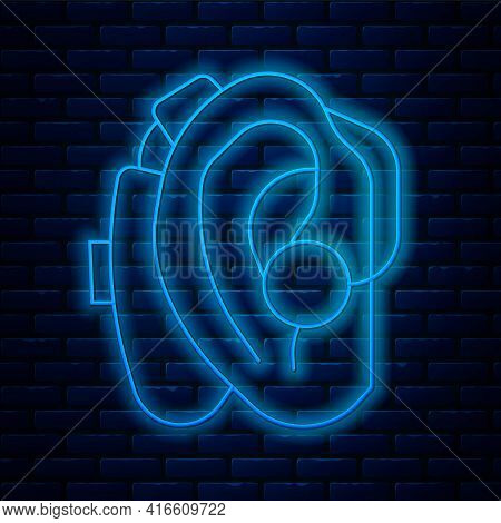 Glowing Neon Line Hearing Aid Icon Isolated On Brick Wall Background. Hearing And Ear. Vector