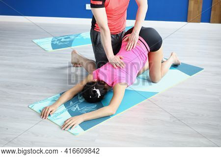 Trainer Helping Young Woman To Do Sports Exercises In Gym