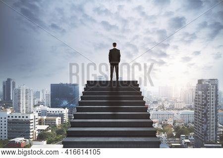 Leadership Concept With Businessman Silhouette Back On The Top Of Stairs Above Sunny City