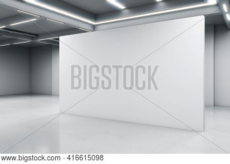 Empty Big White Room With A White Blank Concrete Wall In The Middle, Artificially Lighted, Showroom