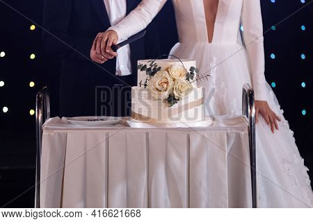 Bride And Groom Cut The Wedding Cake. The Cake Is Decorated With White-colored Roses. Groom Is Dress
