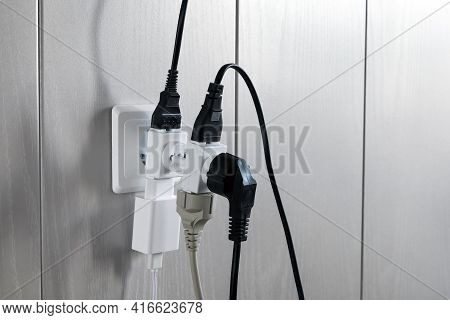 Multiple Plugs In Wall Electrical Outlet Is Dangerous Overload, Close-up With Copy Space