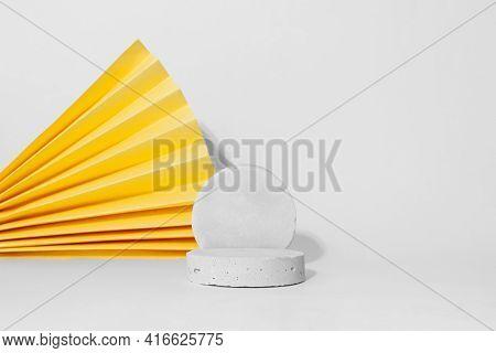 Gray Cocncrete Circle Shaped Pedestals, Yellow Paper Fan, White Background, Copy Space. Podium Mocku