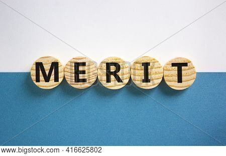 Merit Symbol. Wooden Circles With The Word 'merit'. Beautiful White And Blue Background, Copy Space.