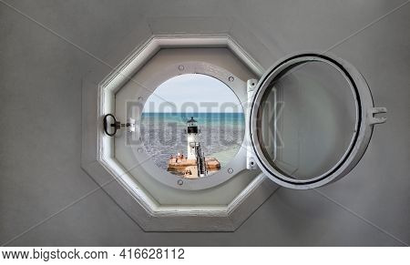 View of a lake from inside of a lighthouse porthole window, focus on window latch and wooden frame, grunge old textured walls, muddy river water flows out into the lake