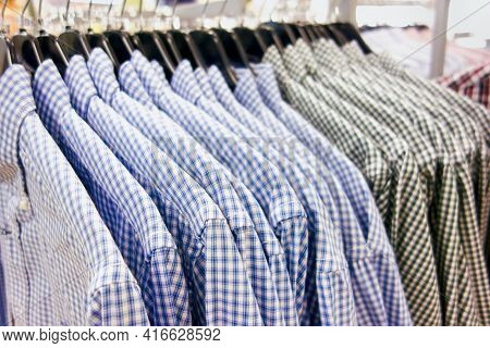 Checkered Shirts Hanging On Hangers In A Clothing Store