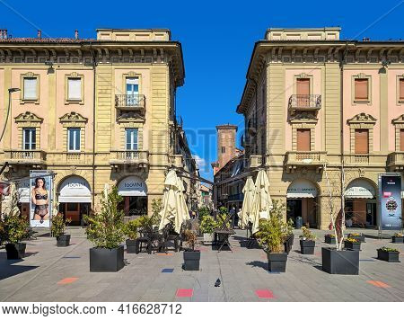 ALBA, ITALY - MARCH 20, 2021: Piazza Ferrero, buildings and medieval tower under blue sky in old Alba - small town in Piedmont, famous for white truffles and wine production.
