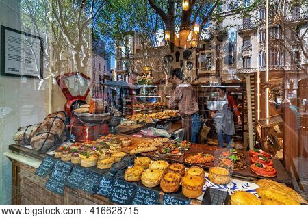 PALMA, SPAIN - APRIL 11, 2019: Street reflection in a glass showcase and freshly baked pastries of Fornet de la Soca - famous family-run bakery specializing in traditional cuisine of Mallorca.