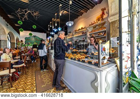 PALMA, SPAIN - APRIL 11, 2019: People inside of Forn del Santo Cristo - famous bakery in historic center of Palma, founded in 1910, offers ensimadas and other traditional Mallorcan specialties.