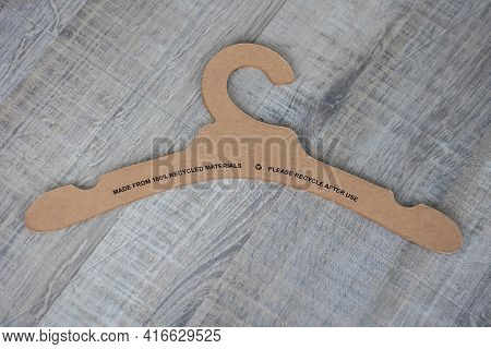 A Portrait Of A Recyclable Clothes Hanger Made Of Paper And Cardboard Lying On A Wooden Table Withou
