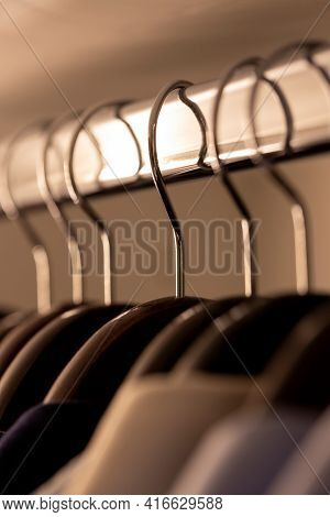 A Portrait Of Wooden Clothes Hangers Hanging With Their Metal Hooks From A Metal Bar In A Wardrobe C