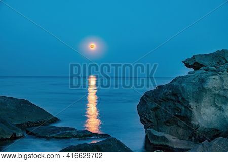 Super Full Blood Moon And Moon Light Over The Sea. Full Red Moon With Reflection In Water With Detai