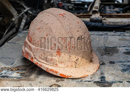 Construction Protective Helmet Covered With Mud And Drilling Mud. Concept, Work Drilling Of Geologic