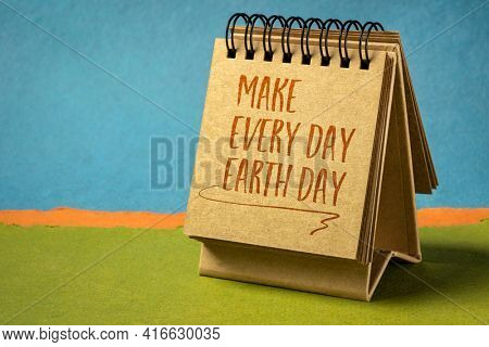 make everyday earth day inspirational note - handwriting in a small desktop calendar against abstract paper landscape, environmental concept