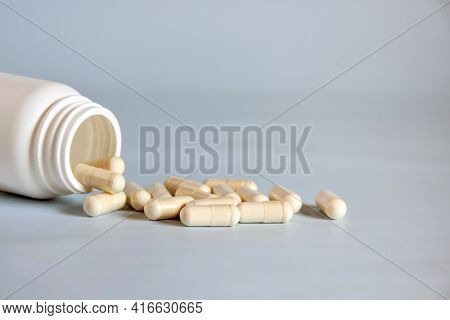 Natural Yellow Pressed Medicinal Herb,pills In Open Upturned Plastic Jar On Table Front. Alternative