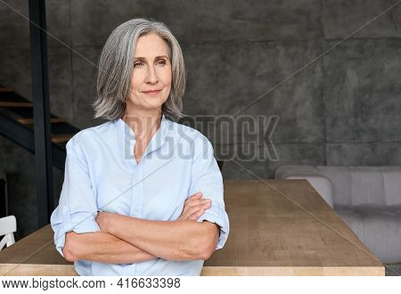 Thoughtful Mature 60s Old Woman Standing Arms Crossed In Home Office. Portrait Of Senior Adult Profe