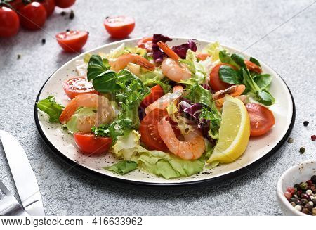 Mix Salad With Tomatoes And Grilled Shrimps With Sauce And Clematis On The Kitchen Table. Concrete F