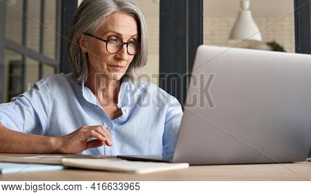 Mature Adult 60s Aged Woman Working At Laptop Watching Video Conference Webinar Training, Virtual Me