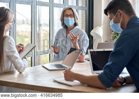 Senior Older Educator Working With Computers In Office With Team Wearing Medical Masks During Covid