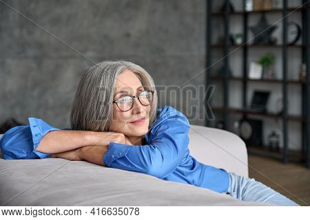 Mature Peaceful 60s Middle Age Lady Sitting Relaxing At Home. Senior Elder Serene Woman In Glasses L