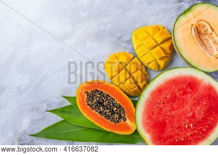 Assortment Of Tropical Fruits In A Cut On A Gray Marble Background. Ripe Watermelon, Papaya, Mango A