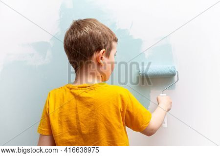Little boy is painting the walls of his room with a roller in turquoise color.